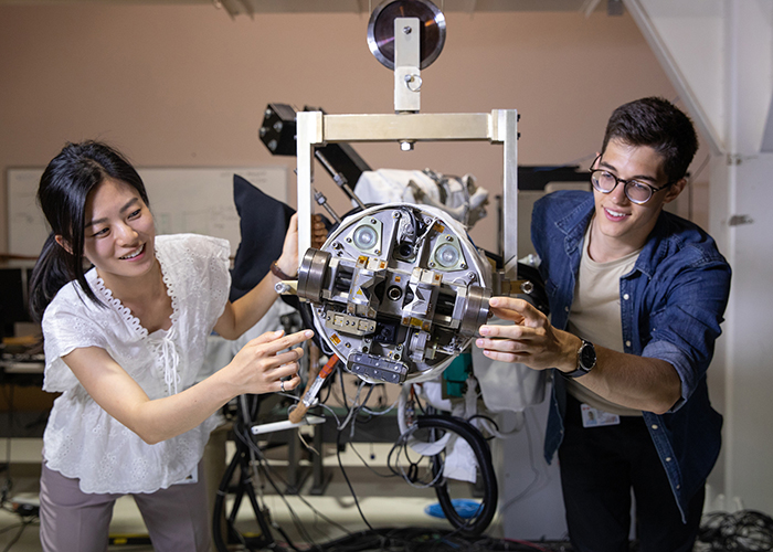 MechE student David Pecile (right), who is currently completing his PEY at MDA Corporation, works on part of the Next-Generation Canadarm project alongside MDA employee Lauren Haensel (left) at MDA Corporation's offices in Brampton, ON. (Credit: Laura Pedersen)